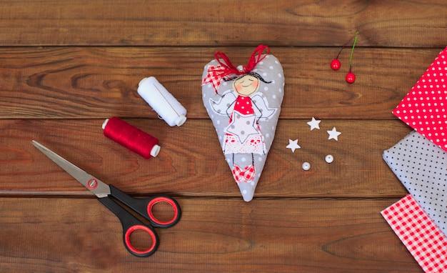 Het maken van textiel met de hand gemaakt kerstmisspeelgoed op houten achtergrond