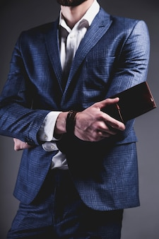 Het manierportret van de jonge zakenman knappe modelmens kleedde zich in elegant blauw kostuum op grijs.