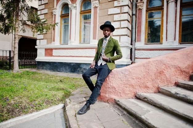 Het manierportret van de zwarte afrikaanse amerikaanse mens op groen fluweeljasje en zwarte hoed zit op treden oud herenhuis als achtergrond