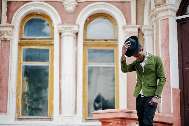 Het manierportret van de zwarte afrikaanse amerikaanse mens op het groene fluweeljasje blijft op treden en draagt zijn zwart hoed oud herenhuis als achtergrond.