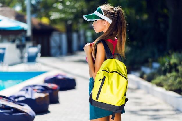 Het manierportret van jonge mooie vrouw in modieuze sportenuniform met neonrugzak en transparant vizier gaat tennissen in warme zonnige de zomerdag.