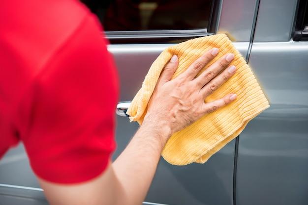 Het mannelijke autopersoneel van de zorgdienst schoonmakende autodeur met microfiberdoek