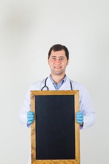 Het mannelijke bord van de artsenholding in witte laag, handschoenen en op zoek vrolijk. vooraanzicht.