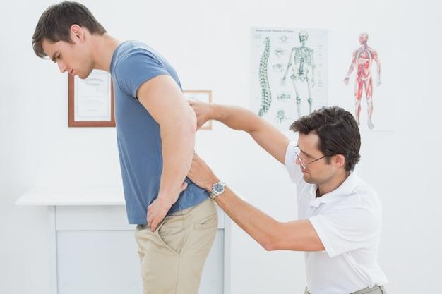 Het mannelijke fysiotherapeut onderzoeken bemant terug in bureau