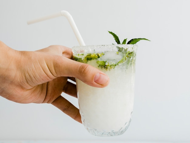 Het mannelijke glas van de handholding cocktail met pepermunt en stro