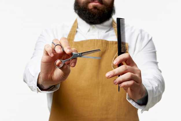 Het mannelijke kapper en herenkapper stellen met schaar en kapperkam