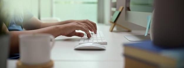 Het mannelijke ondernemer typen op computerapparaat op wit bureau in moderne bureauruimte