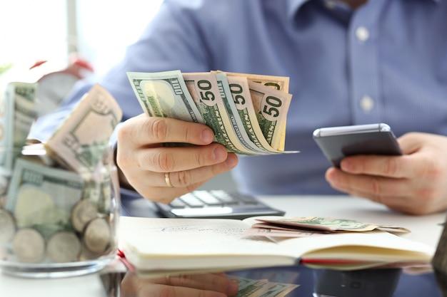 Het mannelijke pak van de handholding van bankbiljetten en cellphone