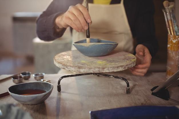 Het mannelijke pottenbakker schilderen op kom