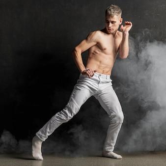 Het mannelijke uitvoerder stellen in jeans met sokken en rook