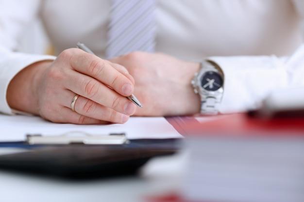 Het mannelijke wapen in kostuum en band houdt zilveren pen vullend programma in blocnote bij de close-up van de bureauwerkplaats. juridisch recht raadplegen hulpgebaar of financieren investeringsadviseur bediende jobinformatie gebaar
