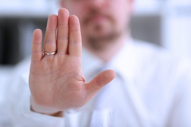 Het mannelijke wapen toont palm tijdens conferentiegesprek aangezien nr in bureauclose-up. suggestie weigeren oplossing argument illustreren aanbod propositie omkoping vraag weg te houden service hoog vijf concept te beschermen