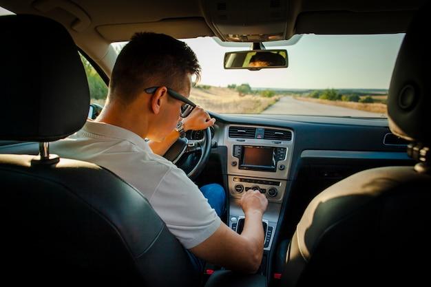 Het mannelijke wiel van de bestuurdersholding en het aanpassen van radio