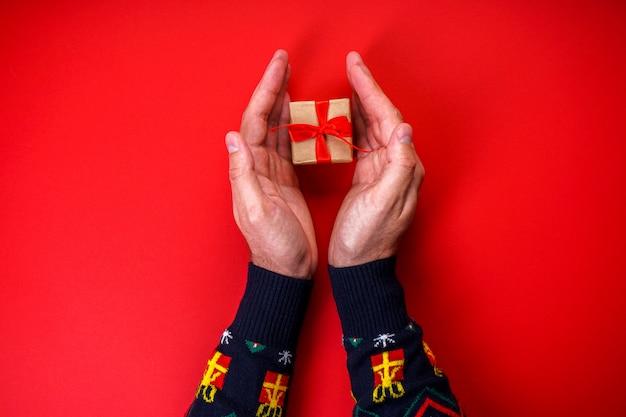 Het mannetje dient een kerstmissweater in met een gift op rood.