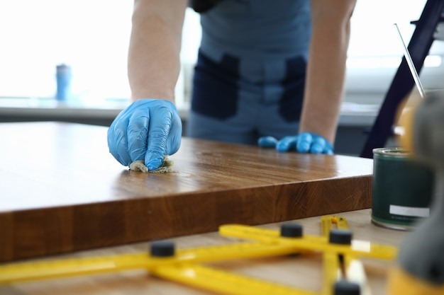 Het mannetje dient het blauwe tafelblad van de rubberhandschoenenolie in