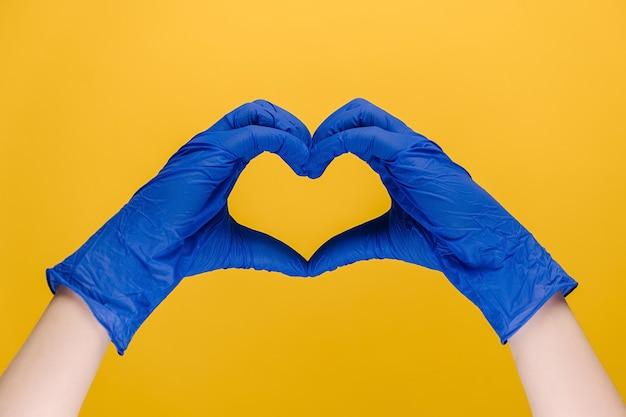 Het mannetje dient medische handschoenen in die hartsymbool maken