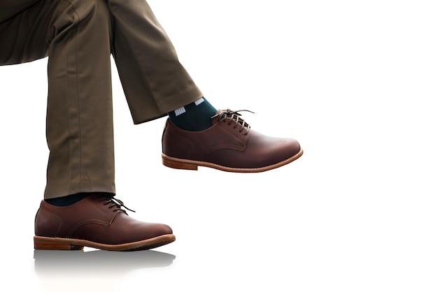 Het mannetje draagt een lange broek en bruine lederen schoenen voor herencollectiekleding