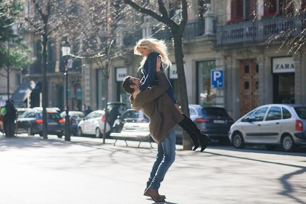 Het mannetje houdt de hand van zijn vrouw vast en kijkt haar teder aan en loopt door de straten van de stad.