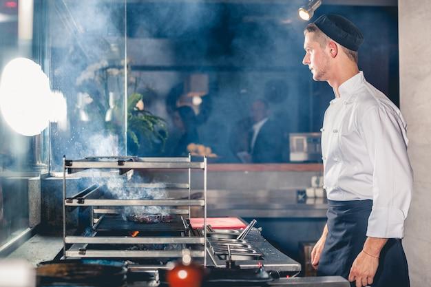 Het mannetje kookt het bereiden van maaltijd bij de grill. eten en drinken concept