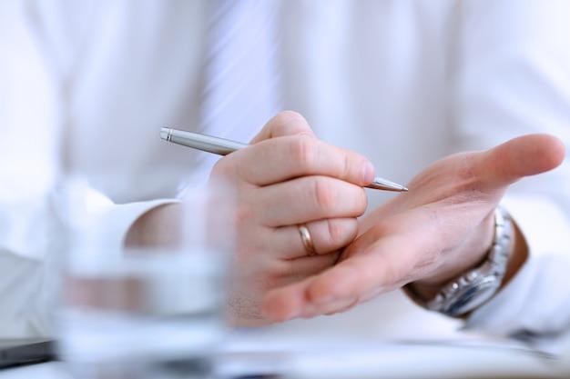 Het mannetje maakt x dwarsnota met zilveren pen bij zijn wapen voor in gedachten houden in bureauclose-up. probeer het lijstconcept niet te vergeten