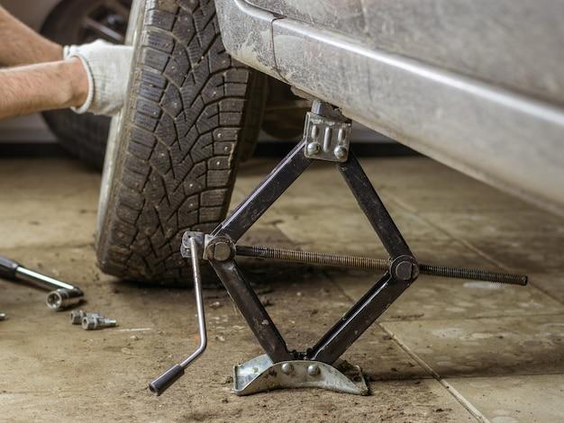 Het mannetje overhandigt het wiel met een bruine auto in de garage.