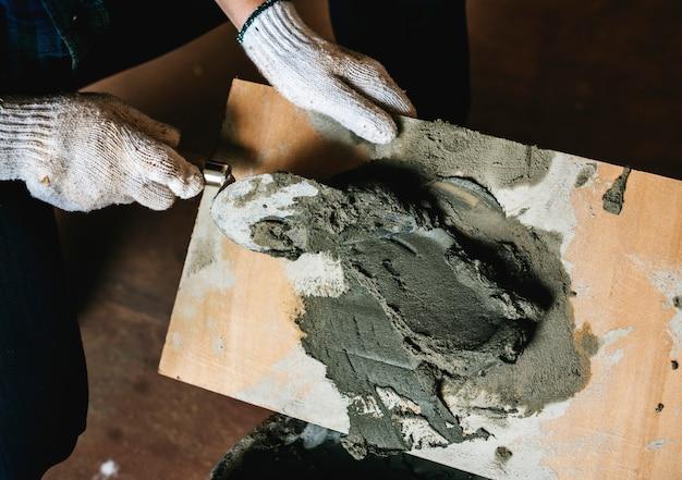Het manusje van alles bereidt cementgebruik voor bouw voor