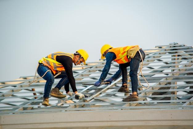 Het manusje van alles die werkt aan installeren het dak, dakwerkerbouwer die aan dakstructuur werken van het bouwen op bouwwerf.