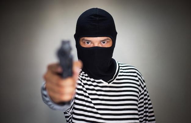 Het masker van de terroristenaard en houdt pistool, kanon, in hand