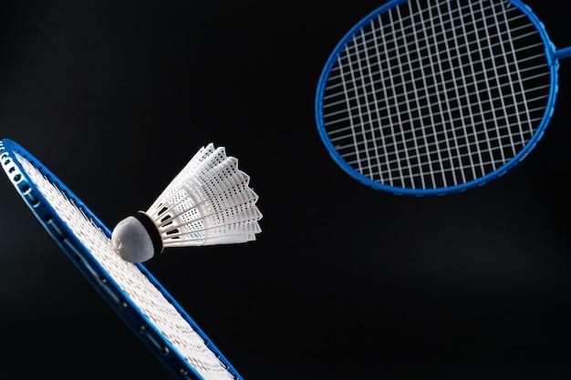 Het materiaal van de badmintonsport op donkere zwarte dichte omhooggaand als achtergrond