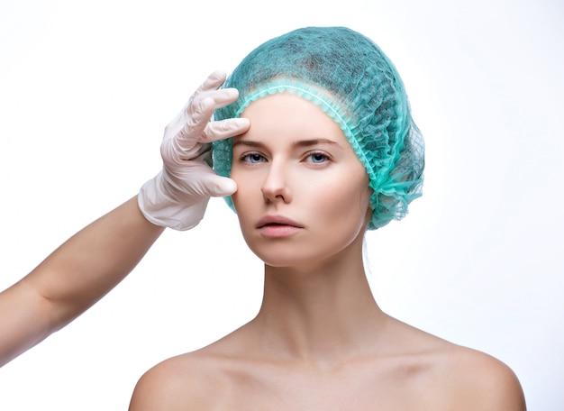 Het medisch onderzoekgezicht van mooie vrouw dient langs handschoen in - close-upportret op wit wordt geïsoleerd dat