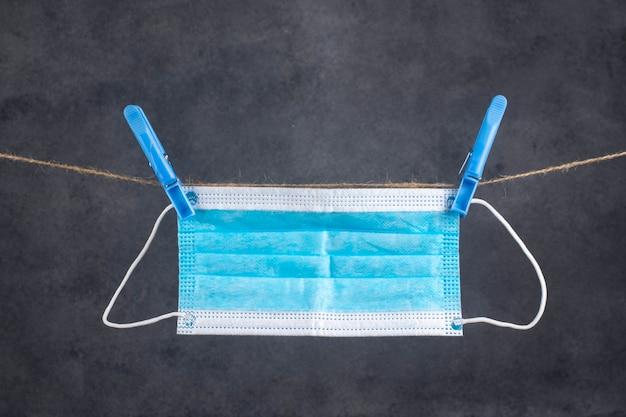 Het medische masker hangt aan een touw.