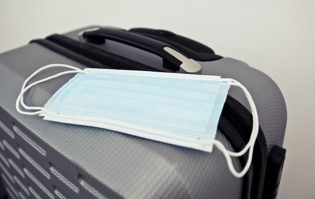 Het medische masker op de koffer als een noodzakelijk ding in reizen in post covid-19 tijd