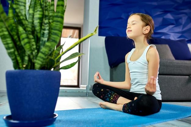 Het mediteren van het meisje in lotusbloem stelt met gesloten ogen