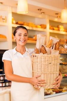 Het meest verse brood voor onze klanten. mooie jonge vrouw in schort die mand met brood vasthoudt en glimlacht terwijl ze in de bakkerij staat
