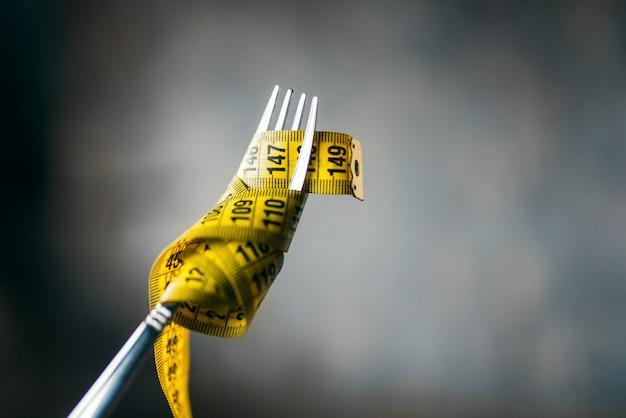 Het meetlint wordt op een vorkclose-up gewikkeld. gewichtsverlies dieet concept