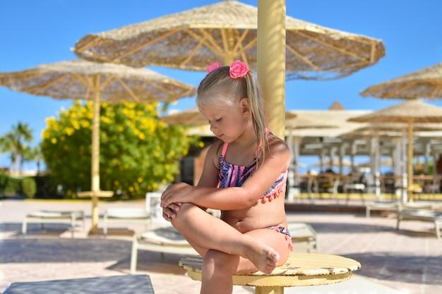 Het meisje ademt uit na het zwemmen in de zee onder een parasol op het strand