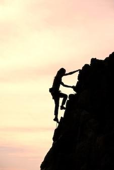 Het meisje alleen verovert de top tijdens een klim