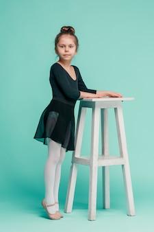 Het meisje als balerinadanser dichtbij stoel op blauwe studio