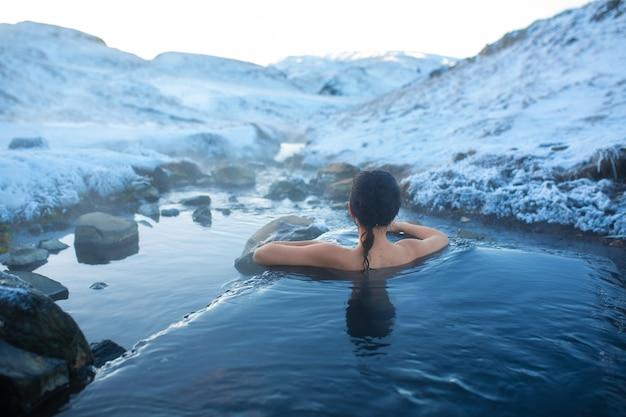 Het meisje baadt in een hete lente in de open lucht met een prachtig uitzicht op de besneeuwde bergen. ongelofelijk ijsland in de winter