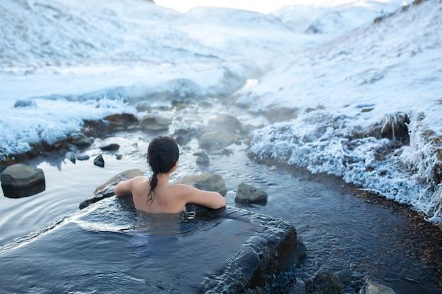 Het meisje baadt in een hete lente in de open lucht met een prachtig uitzicht op de besneeuwde bergen