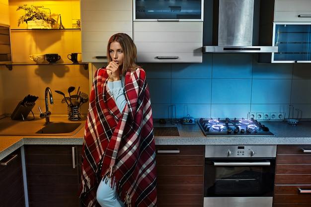 Het meisje bedekte zichzelf met een plaid in de keuken
