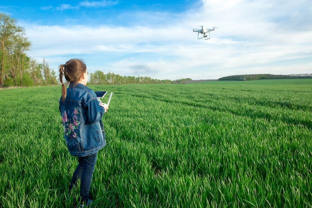 Het meisje bedient de drone met de afstandsbediening in het veld