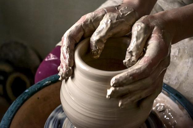 Het meisje beeldhouwt in de close-up van de kleipot. modelleren van klei close-up. blanke man die overdag een vaartuig van witte klei maakt in een snel bewegende cirkel. kunst, creativiteit. oekraïne, culturele tradities. hobby's