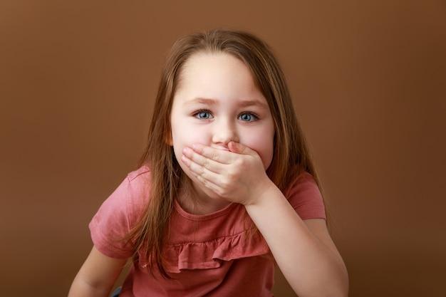 Het meisje behandelt haar mond met haar hand in verrassing