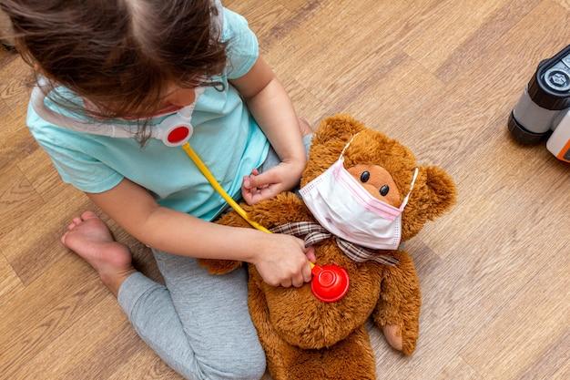 Het meisje behandelt het helen van een stuk speelgoed beer in een medisch masker