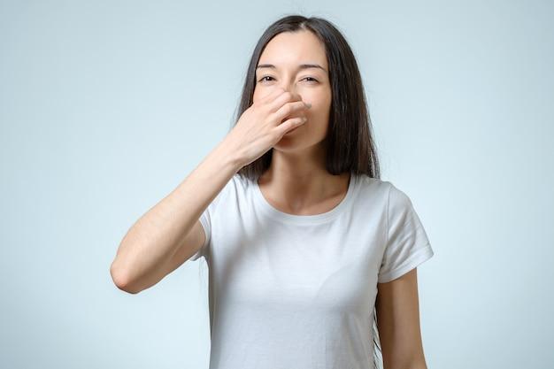 Het meisje behandelt neus met hand die aantoont dat iets stinkt