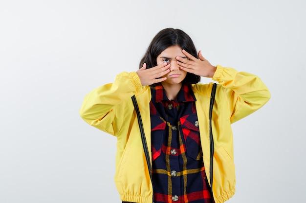 Het meisje behandelt oog met dient gecontroleerd overhemd, jasje in en kijkt ernstig