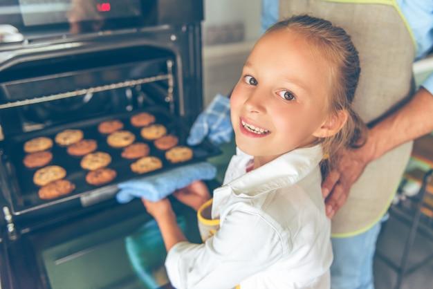 Het meisje bekijkt camera en glimlacht terwijl het maken van koekjes.