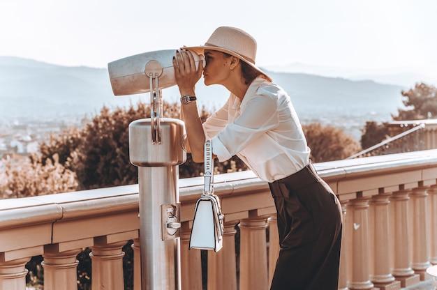 Het meisje bekijkt het panorama van florence door een binoscoop.