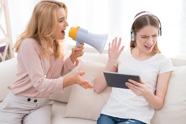Het meisje bekijkt tablet terwijl de moeder tegen haar schreeuwt.